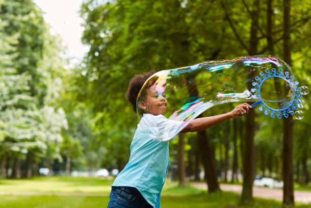 Waist up portrait of cute African-American boy playing with bubbles outdoors in green park holding big bubble wand, copy space